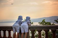 Two little children, boy brothers, looking at landing airplane in the sky ove Stock Photos