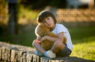 Sweet boy, playing with teddy bear on a small rural path on sunset Stock Photos