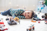 Little child playing with lots of colorful plastic toys indoor Stock Photos