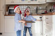 Sweet little children, boy brothers, preparing ginger bread cookies for the o Stock Photos