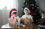 Two sweet boys, brothers, making gingerbread cookies house, decorating at hom Stock Photos
