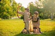 Cute portrait of native american boys with costumes, playing outdoor in the p Stock Photos
