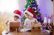 Two sweet boys, brothers, making gingerbread cookies house Stock Photos