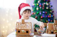 Cute little boy, making gingerbread cookies house for Christmas Stock Photos