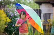 Cute adorable child, boy, playing with colorful umbrella under sprinkling wat Stock Photos