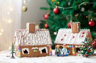 Two gingerbread houses, tree and people sitting on a bench, winter scene Stock Photos