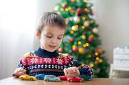 Adorable little preschool boy, playing with toy cars at home on Christmas Stock Photos