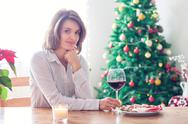 Young woman, drinking wine and having snack at home on christmas Stock Photos