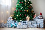 Christmas tree with lots of presents under the tree, lights and toys Stock Photos