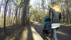 Mother push baby pushchair in spring park path. 4K Stock Footage