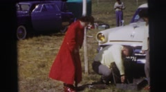 1955: two well dressed men and a woman appearing to be inflating a tire LE MANS Stock Footage