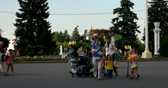 In the square near the fountain at ENEA people walk with young children Stock Footage