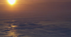 Beautiful sunset glare on sea ice with blizzard blowing snow Stock Footage