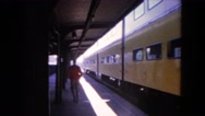 1964: man walking away on a platform as a yellow train leaves the station. Stock Footage