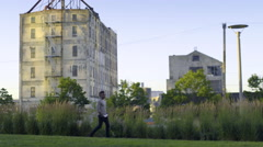 Man Goes For A Walk In City Park, Cool Industrial Buildings In Background Stock Footage