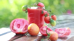Tomato juice and fresh tomatoes in the garden in summer Stock Footage