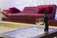 Interior with a coffee table, a sofa and a bottle of wine Stock Photos