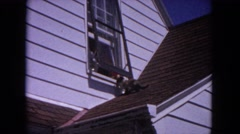 1964: cat climbing from roof into open upper story window EVANSTON, ILLINOIS Stock Footage