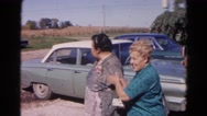 1968: two heavy set women standing beside a car on the side of the road Stock Footage
