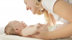 Closeup shot of beautiful young mother kissing her baby son lying on bed in f Stock Footage
