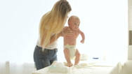 Young mother holding her baby son and teaching him how to walk. Cute boy maki Stock Footage