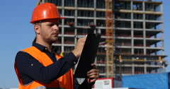 Young Engineer Man Write on a Clipboard Under Construction Building Foreman Work Stock Footage