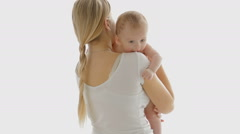Beautiful young woman hugging her 3 years old baby boy in front of big window Stock Footage