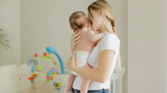 Beautiful smiling woman holding her 3 months old baby boy on hands in child's Stock Footage