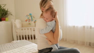 Beautiful young mother sitting on bed and holding her 3 months old baby boy Stock Footage
