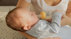 Closeup shot of young mother holding her 3 months old baby boy and feeding wi Stock Footage