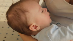 Closeup shot of cute baby boy falling asleep on mothers hands Stock Footage