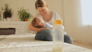Beautiful young mother sitting on bed and rocking her 3 months old baby after Stock Footage