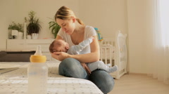 Dolly shot of happy young mother rocking her baby to sleep on bed Stock Footage