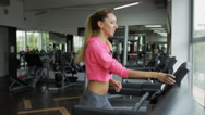 Adult sport woman running on treadmill in gym Stock Footage