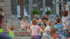 Children are having fun bursting the bubbles in front of a town hall Stock Footage