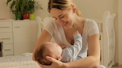 Happy young mother rocking her 3 months old baby boy on bed at bedroom Stock Footage