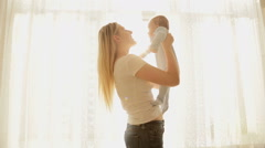 Happy young mother and baby boy at sun rays shining through big window Stock Footage