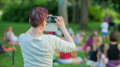 Woman is taking pictures during a concert in the park Stock Footage
