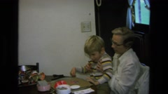 1975: mother helping the boy to complete a diagram on the board CALIFORNIA Stock Footage
