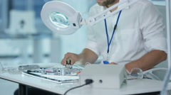 4K Electronics engineer working in the lab checking circuitry & microchips Stock Footage