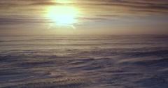 Sun near horizon through clouds in blizzard over tundra Stock Footage