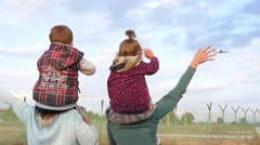 Two woman with a child on shoulders joyfully greeted a plane landing by airport Stock Footage