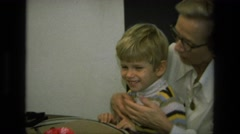 1975: grandma having family time with grandson showing photographs CALIFORNIA Stock Footage