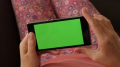 Woman relaxing in home ambient while on green screen smartphone Arkistovideo
