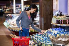 Woman selecting dairy products in grocery section Stock Photos