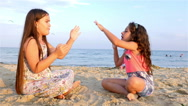 Two little girls playing on the sea beach Stock Footage