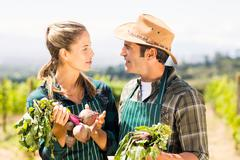 Happy farmer couple holding leafy vegetables Stock Photos