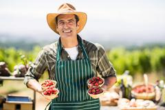 Portrait of a smiling farmer holding bowls of strawberries Stock Photos