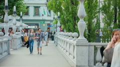 Young couple is walking over the bridge in the main square Stock Footage