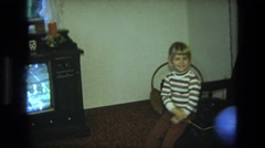 1975: young boy sitting on a chair in the middle of the room watching tv  Stock Footage